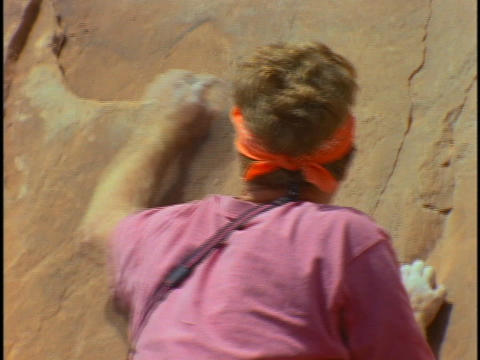 A young man scales a steep, rock face Stock Video Footage