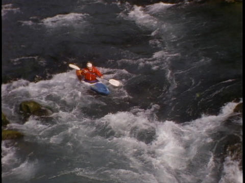 A kayaker plunges down steep rapids Stock Video Footage