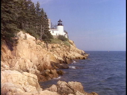 A white lighthouse overlooks the sea on the Maine coast Stock Video Footage
