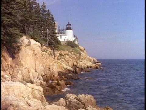 A white lighthouse overlooks the sea on the Maine coast Footage