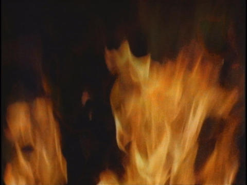 Flames flicker against a night sky Stock Video Footage