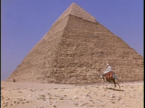 A man rides a camel next to a pyramid Live Action