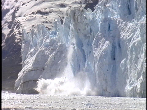 A large chunk of an Alaskan glacier falls into the sea Stock Video Footage