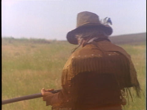 A mountain man dressed in buckskin, aims his rifle Stock Video Footage