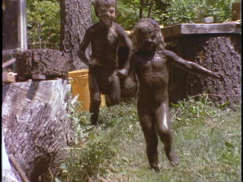children, covered in mud, slide into a muddy hole Stock Video Footage