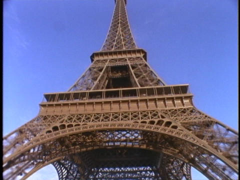 Visitors sit under the Eiffel Tower in Paris, France Stock Video Footage