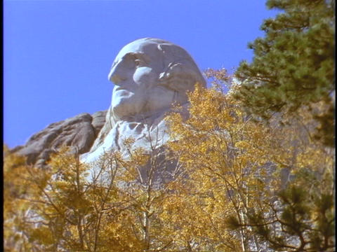 George Washington's head appears above autumn leaves at... Stock Video Footage