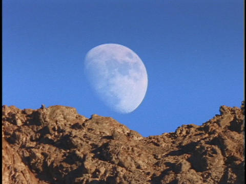 The moon rises from behind a rocky mountaintop Footage