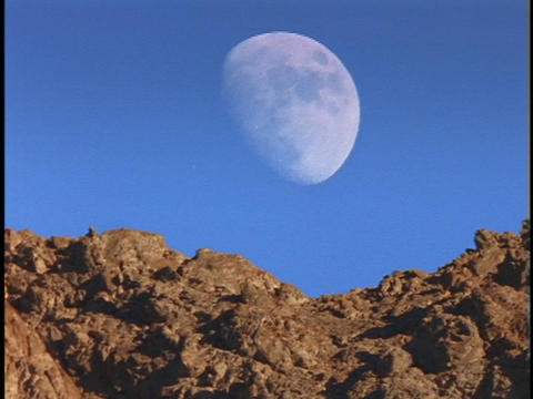 The moon rises from behind a rocky mountaintop Stock Video Footage
