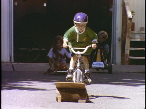 Children ride and jump ramps on bicycles and toy vehicles Footage