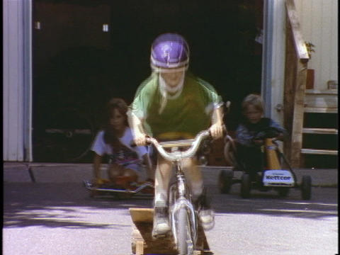 Children ride and jump ramps on bicycles and toy vehicles Stock Video Footage