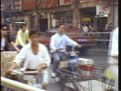 Crowds of bicyclists ride down a street in China Stock Video Footage