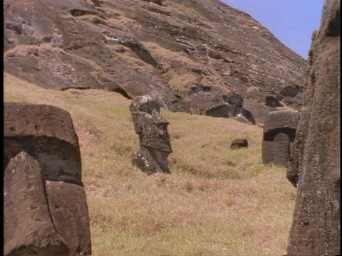 Ancient stone sculptures sit at random in a field on... Stock Video Footage