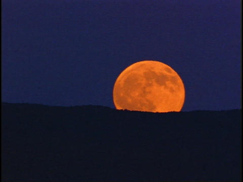 An orange moon rises behind a dark horizon Stock Video Footage