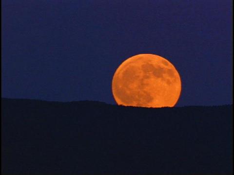 An orange moon rises behind a dark horizon Stock Video Footage