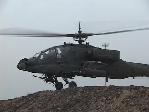 An Apache helicopter lifts off from rough terrain Live Action