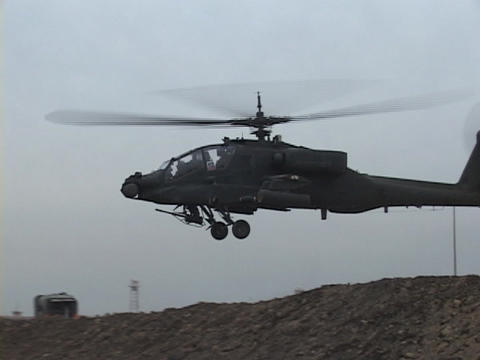 An Apache helicopter lifts off from rough terrain Stock Video Footage