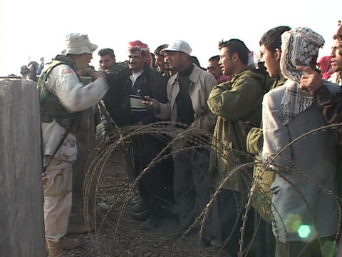 U.S. soldier on a military base talks to Iraqi people... Stock Video Footage