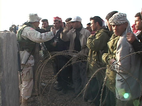 U.S. soldier on a military base talks to Iraqi people waiting for work Footage