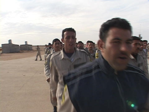 Iraqi troops march along a road on the military base Footage