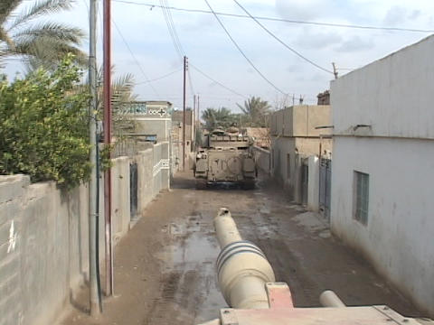Abrams tanks move through an Iraq village Stock Video Footage