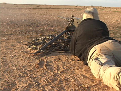 A U.S. soldier fires a machine gun in combat Footage