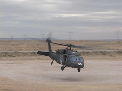 A Black hawk helicopter lifts off from the desert ground Footage