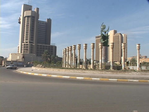 Traffic crosses in front of skyscrapers in Baghdad Stock Video Footage