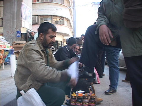 A line of men shine shoes on the streets of Baghdad Stock Video Footage