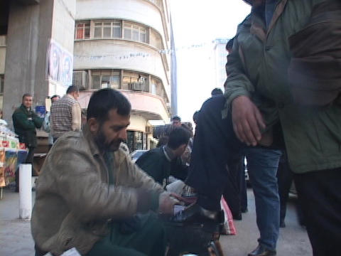 A line of men shine shoes on the streets of Baghdad Footage