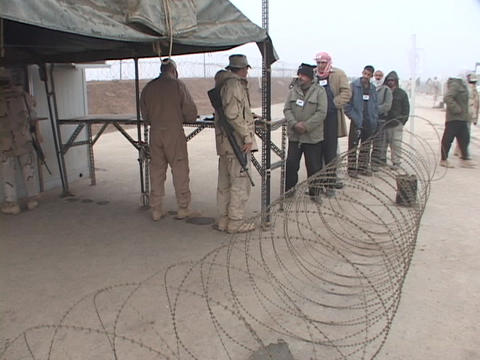 Iraqi citizens line up to get work at a U.S. military base Stock Video Footage