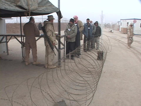 Iraqi citizens line up to get work at a U.S. military base Footage