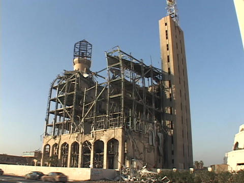 Traffic passes by a destroyed building in worn-torn Baghdad, Iraq Footage