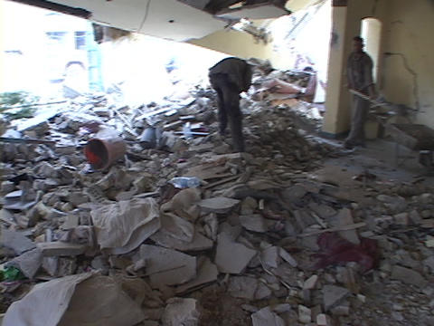 Men shovel rubble in a destroyed building of war-torn... Stock Video Footage