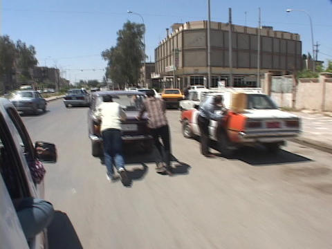 Iraqis push cars and look for gas to siphon in Baghdad Stock Video Footage