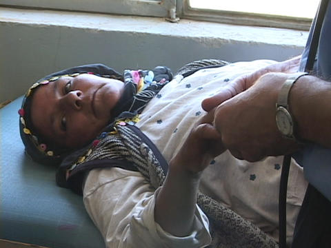 A doctor examines a wounded Iraqi woman's hand in a hospital, a casualty of war Footage