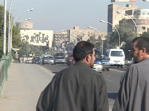 Traffic and pedestrians pass on a busy Baghdad street Stock Video Footage
