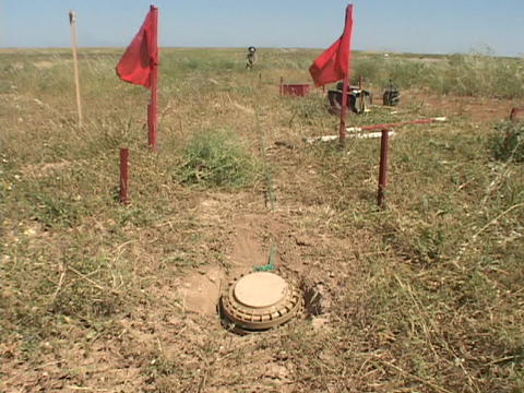 A land mine removal expert pulls on a land mine in Iraq Footage