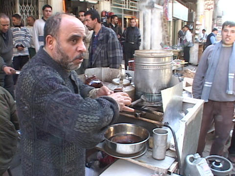 An Iraqi street vendor serves hot tea as other Iraqi men watch Footage