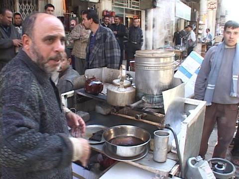 An Iraqi street vendor serves hot tea as other Iraqi men... Stock Video Footage