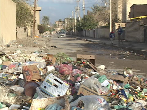 Cars and Iraqi pedestrians make their way past trash... Stock Video Footage