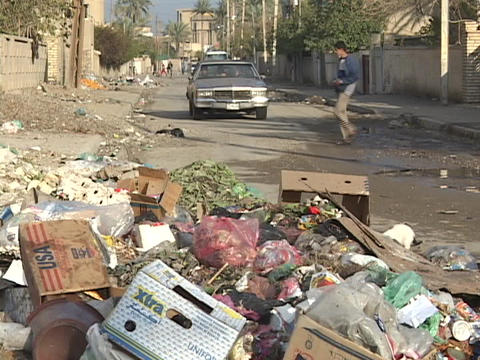 Cars and Iraqi pedestrians make their way past trash accumulating on war-torn Baghdad streets Footage