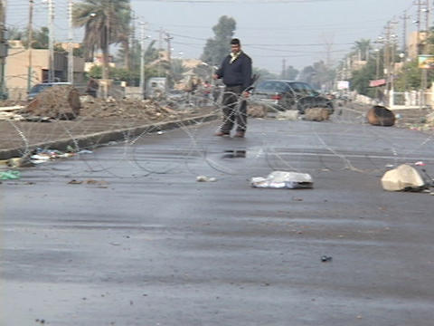 An Iraqi man stands guard at a crude roadblock on a... Stock Video Footage
