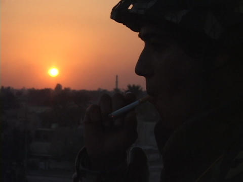 A soldier smokes a cigarette while manning a guard post in Baghdad, Iraq Footage