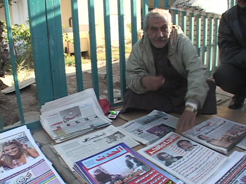 An Iraqi vendor shows a newspaper with headlines of... Stock Video Footage