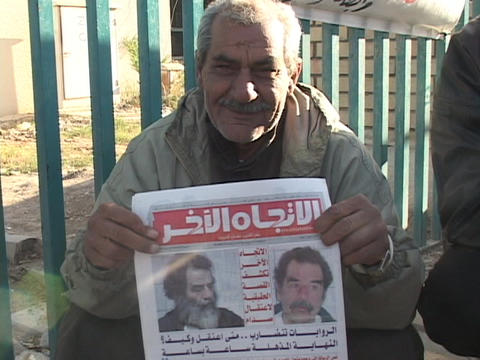 An Iraqi vendor shows a newspaper with headlines of Saddam Hussein's capture Footage