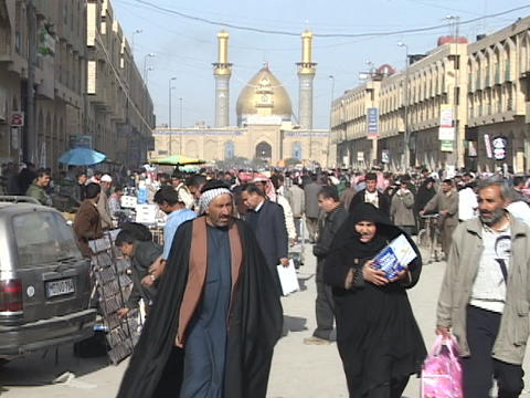 A beautiful mosque stands behind a busy shopping area in downtown Baghdad, Iraq Footage