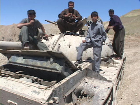 Iraqi men and boys sit on a destroyed tank during the Iraq War Footage