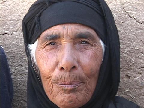 A mature Muslim woman leans against a wall in rural Iraq Stock Video Footage