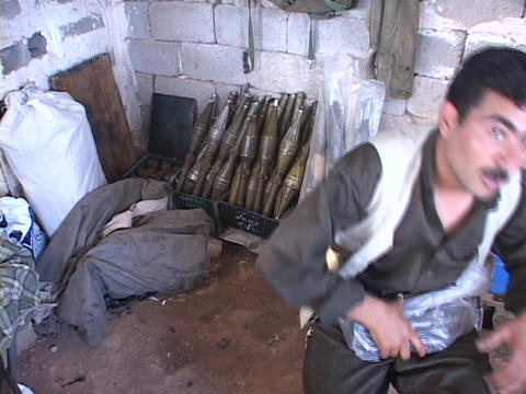 A weapons dealer in Northern Iraq proudly poses with his arsenal Footage